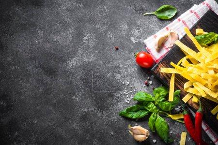 Photo pour Alimentation italienne. Pâtes, tomates, fromage, basilic et huile d'olive sur table en pierre noire. Vue du dessus, Espace de copie . - image libre de droit