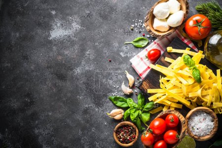 Photo for Italian food background. Pasta, tomatoes, cheese, basil and olive oil on black stone table. Top view, Copy space. - Royalty Free Image