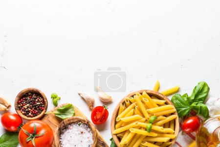 Photo for Food cooking ingredients background. Pasta, tomatoes, herbs and vegetables on white table. Top view with copy space. - Royalty Free Image