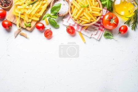Foto de Fondo de ingredientes cocción de alimentos. Pasta, tomates, hierbas y hortalizas en mesa blanca. Vista superior con espacio de copia - Imagen libre de derechos