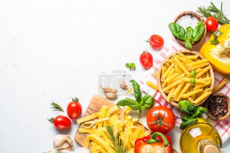 Photo for Healthy food background. Pasta, tomatoes, herbs and vegetables on white table. Top view with copy space. - Royalty Free Image
