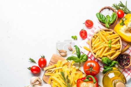Foto de Fondo de alimentos saludables. Pasta, tomates, hierbas y hortalizas en mesa blanca. Vista superior con espacio de copia - Imagen libre de derechos