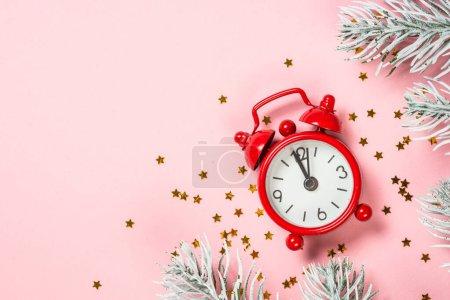 Photo pour Noël fond plat laïc avec horloge rouge, paillettes et décorations de Noël sur la mise en page rose. Vue supérieure avec espace de copie. - image libre de droit