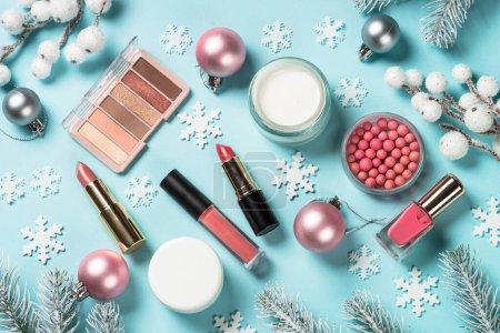 Photo pour Produits de maquillage, produits de soins de la peau avec décorations de Noël. Idée pour le shopping de Noël, cadeaux. Vue en haut sur fond bleu. - image libre de droit