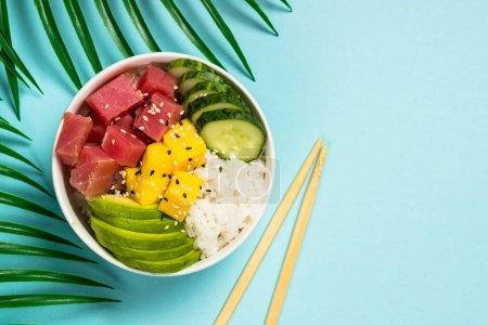 Photo pour Bol de poke de thon avec le riz, l'avocat, la mangue et le concombre sur le fond bleu. Vue du haut. Nourriture asiatique de modèle, nourriture hawaïenne. - image libre de droit