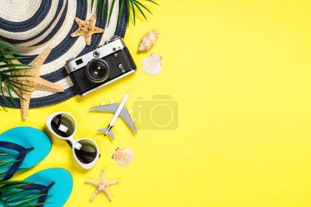 Photo pour Fond plat de voyage d'été. Vieille caméra de film, chapeau, coquille et feuilles de paume sur le fond jaune. - image libre de droit