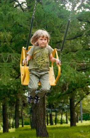Photo for Blonde boy having fun at the playground. Child kid playing on a swing outdoor. Happy active childhood. - Royalty Free Image