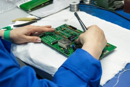 The process of assembling an electronic module. The workers hands place electronic components on the printed circuit board.