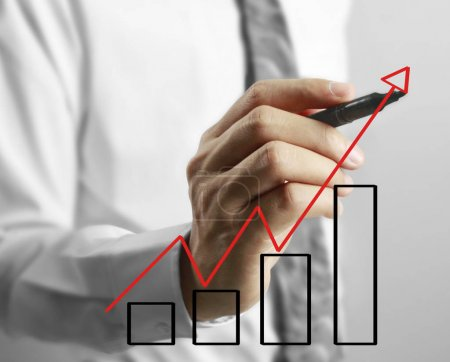 Photo for Businessman drawing graphics growing graph - Royalty Free Image