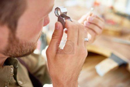 Portret zbliżenie jubilera inspekcji pierścień przez szkło powiększające w warsztacie