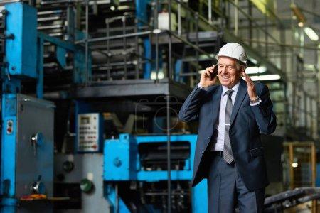 Photo pour Portrait d'homme d'affaires senior portant hardhat s'exprimant par téléphone et souriant dans l'atelier de l'usine moderne, espace copie - image libre de droit
