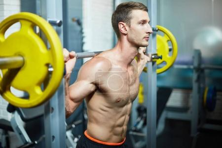 Confident young bodybuilder flexing muscles with barbell while having productive training at modern gym, profile view