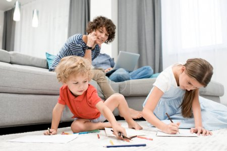 Photo for Portrait of two children drawing pictures sitting on carpet in living room with mom watching them from sofa - Royalty Free Image