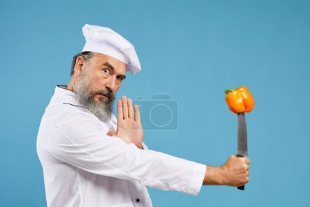 Photo for Portrait of charismatic bearded chef holding sharp knife with bell pepper pierced on it while posing against blue background in studio, copy space - Royalty Free Image