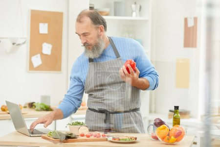 Photo for Portrait of bearded senior man using laptop while cooking dinner in cozy kitchen at home, copy space - Royalty Free Image