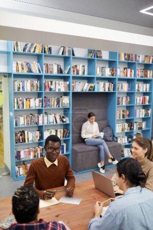 Foto de Vista de gran angular al grupo multiétnico de estudiantes que estudian en la biblioteca moderna de la universidad o universidad, copie el espacio. - Imagen libre de derechos