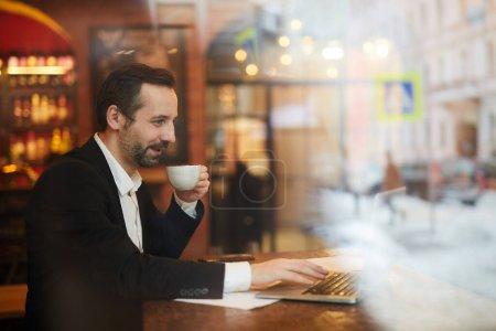 Photo pour Portrait latéral d'un homme d'affaires mature souriant profitant d'une tasse de café assis à table dans un café, espace de copie - image libre de droit