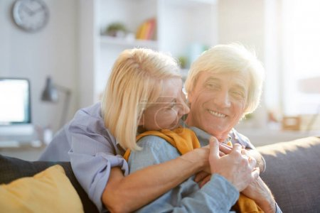 Photo for Warm-toned portrait of carefree senior couple embracing tenderly enjoying leisure time at home lit by sunlight, copy space - Royalty Free Image