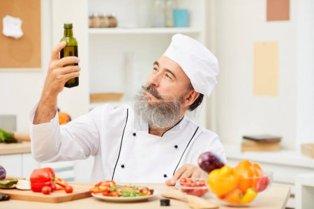 Photo for Portrait of bearded senior chef holding olive oil bottle while cooking meat in restaurant kitchen, copy space - Royalty Free Image