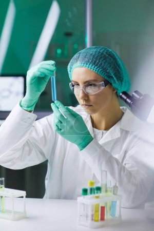 Photo for Portrait of young woman holding test tube while working on scientific research in medical laboratory - Royalty Free Image