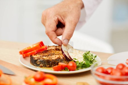 Photo for Close up of unrecognizable chef decorating delicious steak with fresh vegetables, copy space - Royalty Free Image