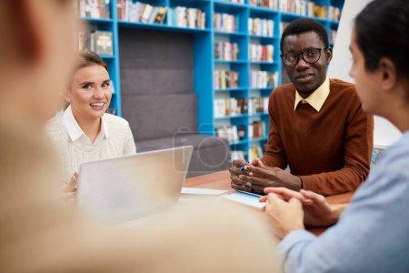 Foto de Grupo multiétnico de estudiantes que trabajan en el proyecto de equipo en la biblioteca, se centran en sonreír el hombre afroamericano líder en la reunión, copiar el espacio. - Imagen libre de derechos