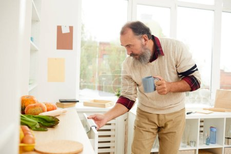 Photo for Side view portrait of bearded senior man opening kitchen cupboards while looking for breakfast in morning, copy space - Royalty Free Image