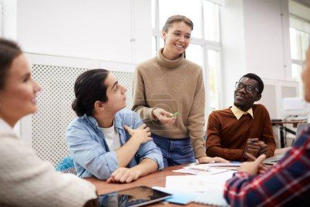 Foto de Un grupo grande de estudiantes trabajando juntos en el proyecto de equipo mientras estudian en la universidad, se centran en sonreír hermosa chica dirigiendo la reunión. - Imagen libre de derechos