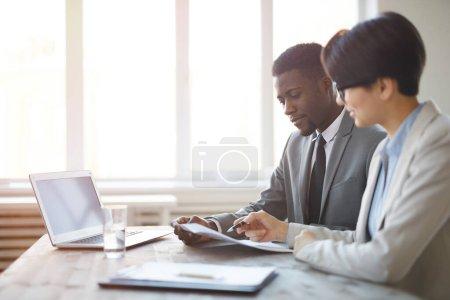 Photo pour Portrait latéral de jeune homme d'affaires africain lisant des documents avec une collègue alors qu'elle était assise sur le lieu de travail contre la fenêtre dans son bureau, espace de copie - image libre de droit