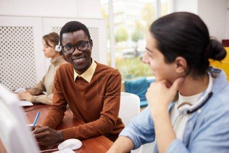Foto de Retrato de un estudiante afroamericano sonriente hablando con su compañero de clase mientras usa computadoras en la biblioteca universitaria, espacio para copiar - Imagen libre de derechos