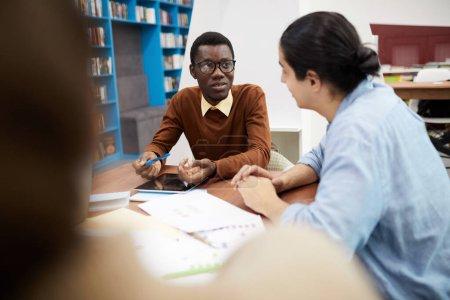 Foto de Grupo multiétnico de estudiantes que trabajan juntos en la biblioteca, se centran en el hombre afroamericano que usa gafas, copia el espacio. - Imagen libre de derechos