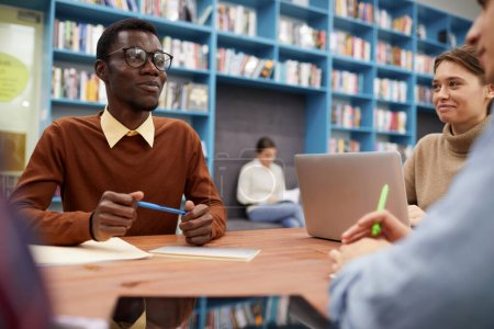 Foto de Retrato del inteligente hombre afroamericano sonriendo alegremente mientras estudiaba con un grupo de estudiantes en la biblioteca, copie el espacio. - Imagen libre de derechos