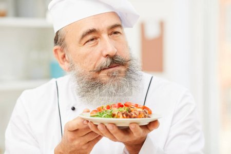 Photo for Portrait of blissful senior chef presenting meat steak while cooking in restaurant kitchen, copy space - Royalty Free Image