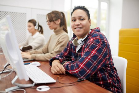 Photo for Portrait of plump young woman smiling at camera while using computer in college library, copy space - Royalty Free Image