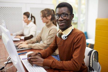 Foto de Retrato del joven afroamericano sonriendo a cámara mientras se utiliza el ordenador en la biblioteca universitaria, copia el espacio. - Imagen libre de derechos
