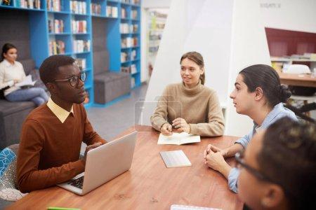 Foto de Visión de alto ángulo en el grupo multiétnico de estudiantes que trabajan en el proyecto de equipo en la biblioteca, enfoque en sonreír el hombre afroamericano líder en la reunión, copiar espacio. - Imagen libre de derechos