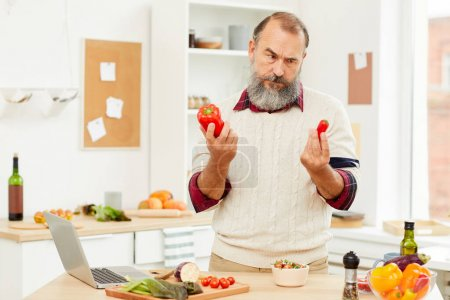 Photo for Waist up portrait of bearded senior man choosing red peppers while cooking vegetables in kitchen, copy space - Royalty Free Image