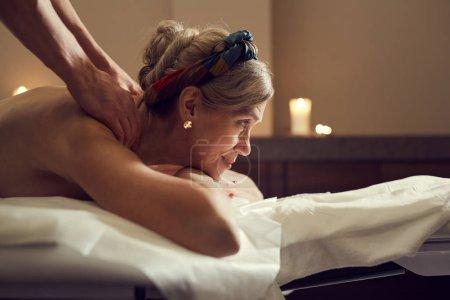 Photo pour Side view portrait of elegant senior woman enjoying massage at luxury Spa center, copy space - image libre de droit