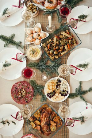 Photo for Top view background of beautiful dinner table decorated with fir branches set for Christmas banquet, copy space - Royalty Free Image