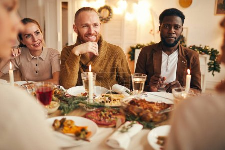 Poirtrait of multi-ethnic group of people enjoying dinner sitting at table with delicious food, focus on smiling bearded man in center