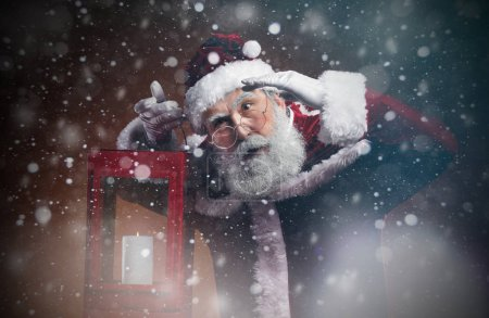 Photo for Waist up portrait of fairytale Santa holding lantern walking through snow storm in the night, copy space - Royalty Free Image
