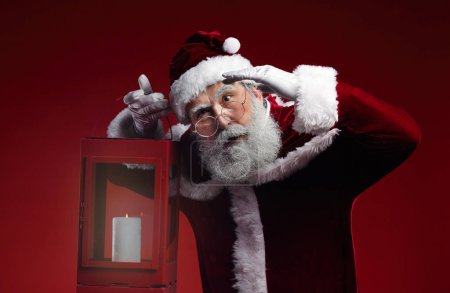 Photo for Waist up portrait of fairytale Santa Claus holding lantern standing against red background in studio - Royalty Free Image