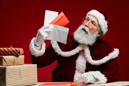 Photo for Portrait of classic Santa Claus holding letters sitting at desk with Christmas presents over red background - Royalty Free Image