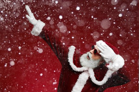 Photo for Waist up portrait of cool Santa dancing over red background with snow falling, copy space - Royalty Free Image