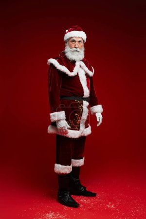 Photo for Full length portrait of classic Santa Claus looking at camera while posing against red background in studio, copy space - Royalty Free Image