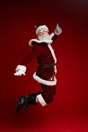 Photo for Full length portrait of classic Santa Claus jumping high against red background in studio, copy space - Royalty Free Image