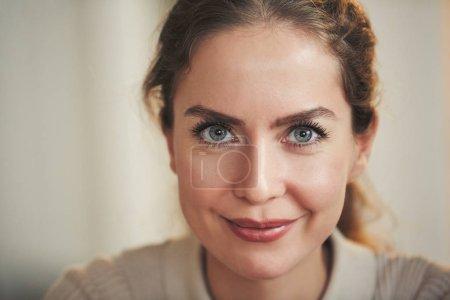 Primer plano retrato de la hermosa mujer adulta sonriendo a la cámara mientras posa en el interior del hogar, espacio de copia