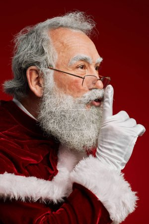 Photo for Side view portrait of classic Santa Claus holding finger to mouth while telling Christmas secrets standing over red background, copy space - Royalty Free Image
