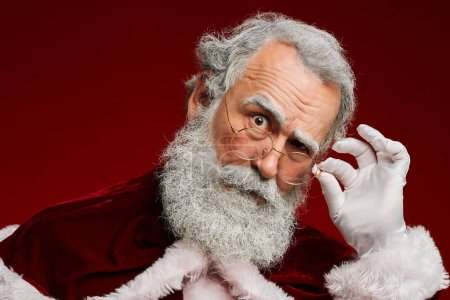 Photo for Head and shoulders portrait of suspicious Santa Claus adjusting glasses while looking at camera over red background, copy space - Royalty Free Image