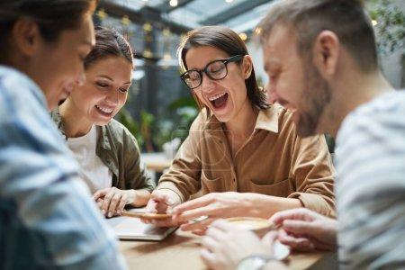 Photo pour Groupe de jeunes contemporains regardant l'écran du smartphone et riant joyeusement tout en profitant du déjeuner ensemble dans un café - image libre de droit